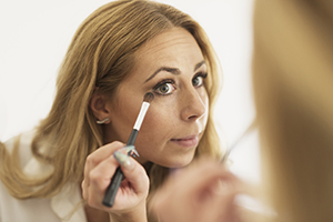 Woman looking in mirror, putting on eye makeup.