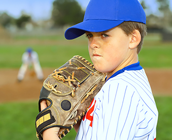 Young boy in softball uniform holding softball glove