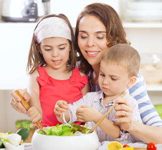 Mother preparing salad with two young children